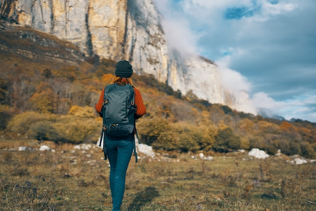Woman with backpack travels in nature and climb mountains
