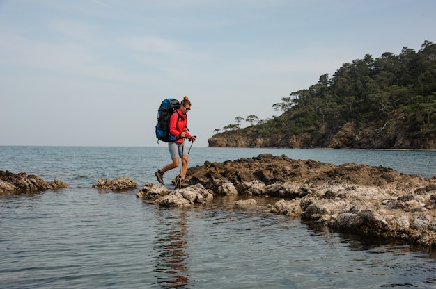 海岸のバックパックトレッキングを持つ女性