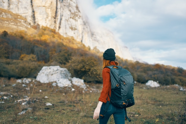 Woman with a backpack walks on nature in the mountains in autumn blue sky rocks