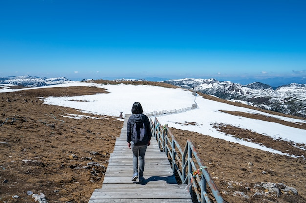 Woman with a backpack walks on the snow mountains