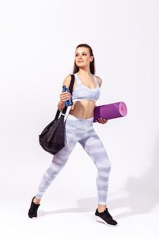 バッグ、フィットネスマット、ボトルを持った女性がジムでトレーニングに急いで、筋肉をポンプでくみます