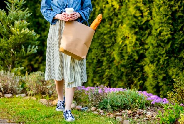 Женщина с багетом в корзине и чашка кофе в саду