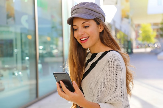 Woman with baker boy hat walking in the street and receive good news on phone
