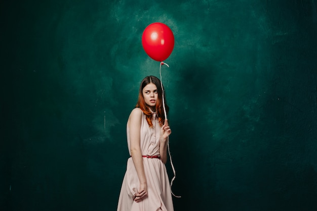 Woman with balloons in her hands in a dress, studio