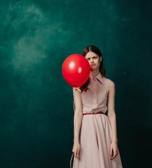 Женщина с воздушными шарами в руках в платье