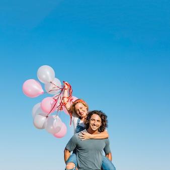 Женщина с воздушными шарами на спине человека