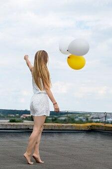 Женщина с воздушными шарами на крыше дома