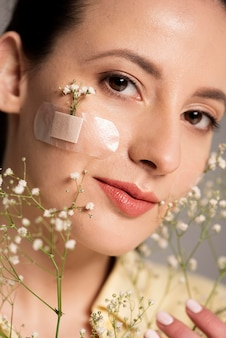 Woman with band aid flower on face
