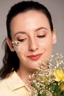 Женщина с цветком лейкопластыря на лице
