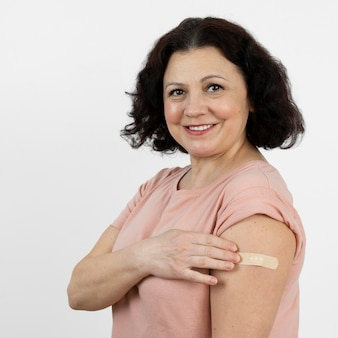 Woman with bandage on arm after vaccine shot