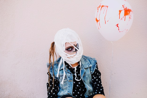 Woman with bandage on face and balloon