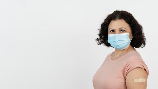 Женщина с повязкой на руке после прививки