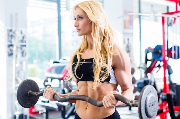 Woman with barbell doing sport in fitness gym
