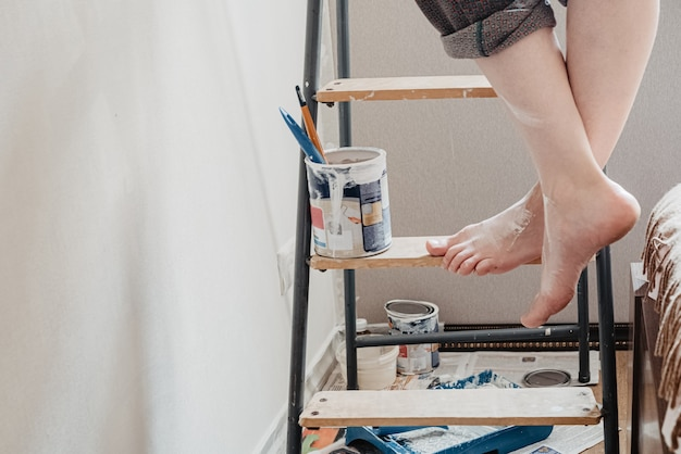 Woman with bare crossed feet stained with white paint stands on stepladder