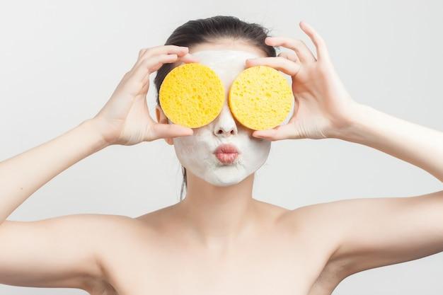 Женщина с голыми ключами кремовая маска скраб губки в руках