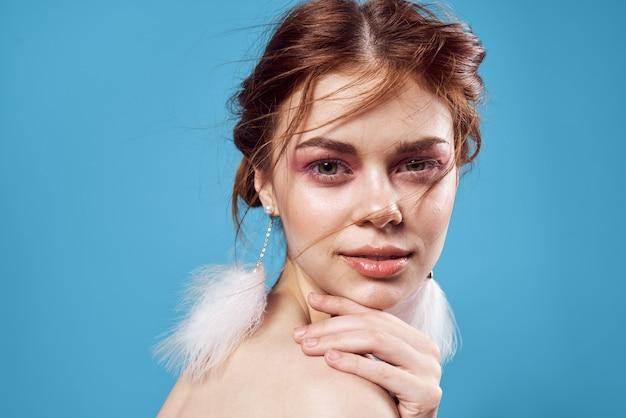 裸の肩と明るいメイクのふわふわイヤリングの女性が魅力的なクローズアップを見てください