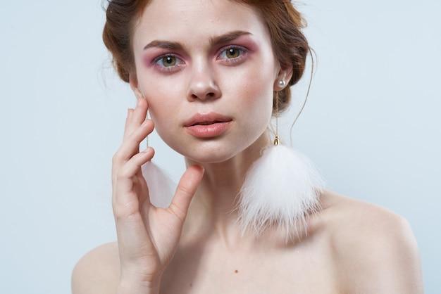 벌거 벗은 어깨와 밝은 메이크업 보석 푹신한 귀걸이를 가진 여자