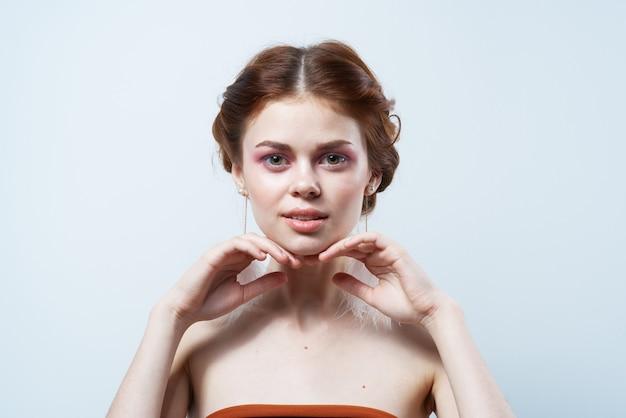 Женщина с открытыми плечами и ярким макияжем украшает пушистые серьги