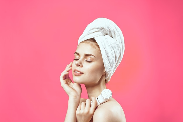 Женщина с обнаженными плечами и косметология для релаксации чистой кожи на розовом фоне