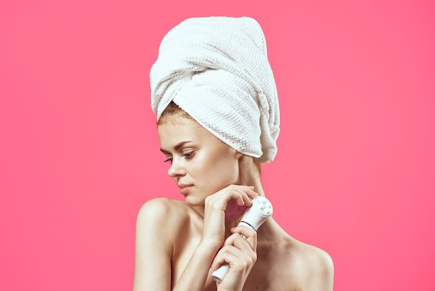 裸の肩と美容のきれいな肌のリラクゼーションピンクの背景を持つ女性