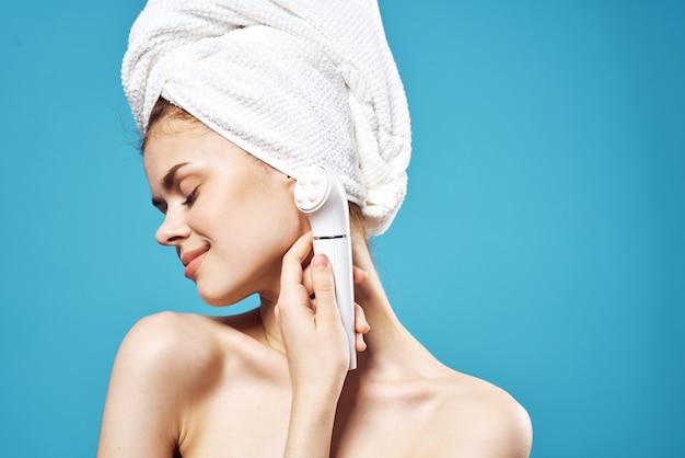 裸の肩と顔の青い背景のために彼女の手でマッサージ師を保持している女性
