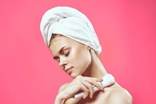 裸の肩と肌のクリーニング美容健康ピンクの背景を持つ女性