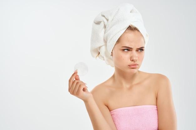 裸の肩と頭にタオルと健康衛生皮膚科を持つ女性