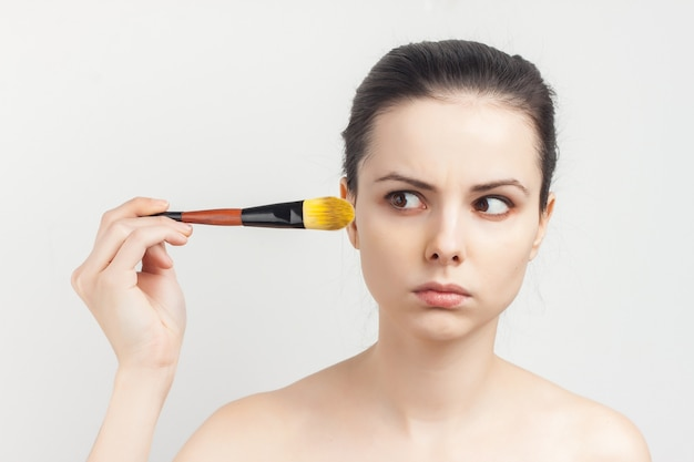 Woman with bare shoulders as face mask brush for applying skin care.