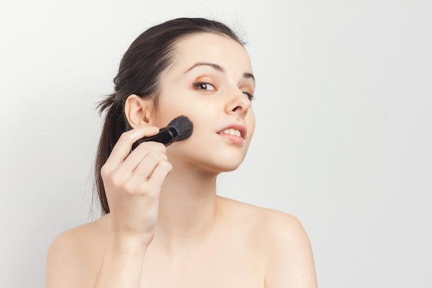 Woman with bare shoulders as face mask brush for applying skin care