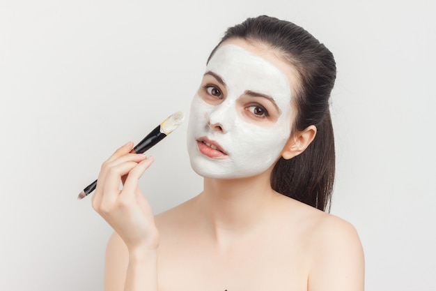 Woman with bare shoulders as face mask brush for applying.