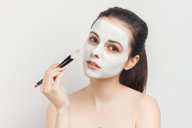 Женщина с открытыми плечами как кисть маски для лица для нанесения.