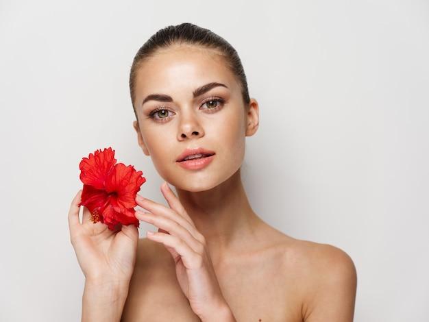 裸の肩を持つ女性の魅力的な外観の化粧品赤い花