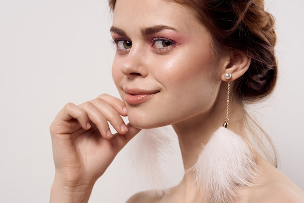 Woman with bare shoulders bright makeup fluffy earrings fashion light background. high quality photo