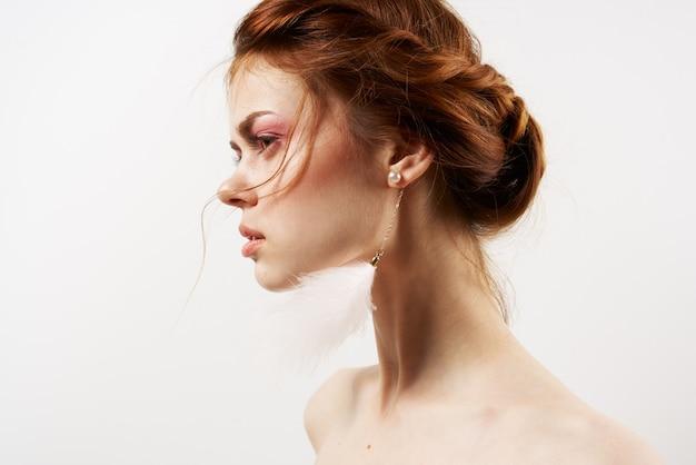 Женщина с обнаженными плечами яркий макияж серьги ювелирные изделия крупным планом