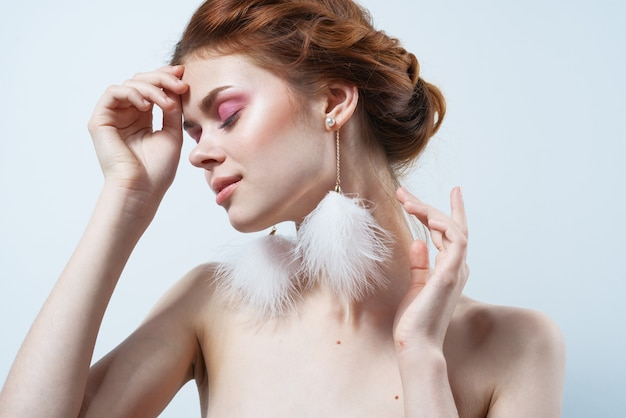 Woman with bare shoulders and bright makeup jewelry fluffy earrings