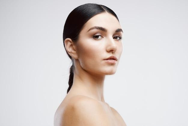 Женщина с обнаженными плечами очищает косметологический уход за кожей. фото высокого качества
