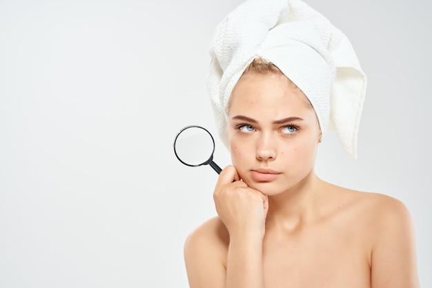 裸の肩を持つ女性は、手に虫眼鏡をきれいにします