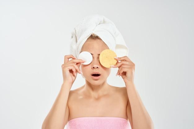 裸の肩のコットンパッドを持つ女性は、肌の問題をクリアします
