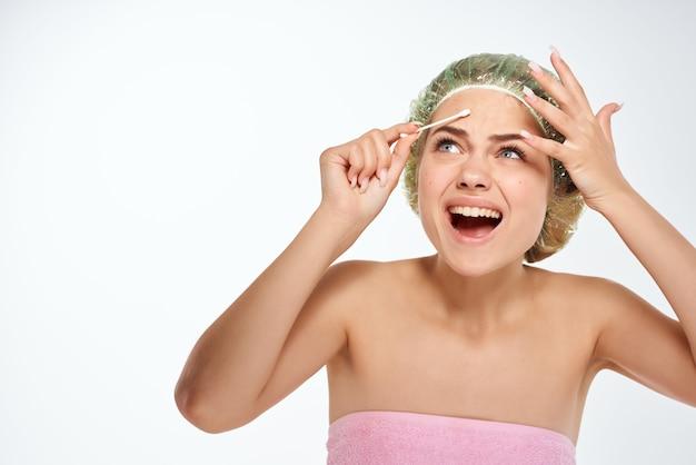 裸の肩を持つ女性綿棒顔の皮膚科