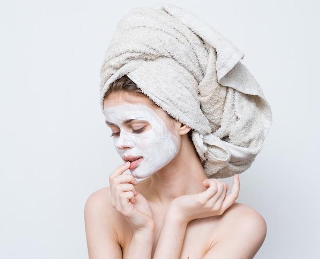Женщина с голыми плечами лицо крем полотенце на голове