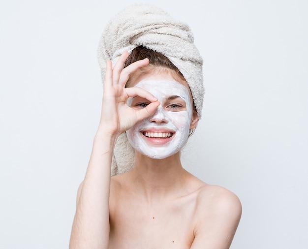 裸の肩を持つ女性はきれいな肌をマスクします