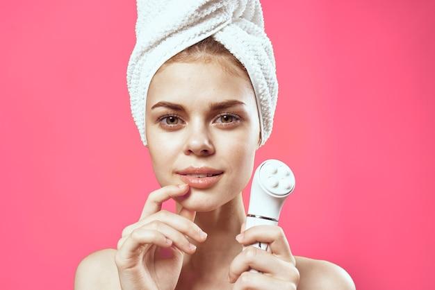 Женщина с голыми плечами массаж лица чистой кожи розовый фон