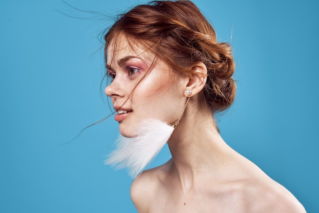 Woman with bare shoulders fluffy earrings bright makeup closeups