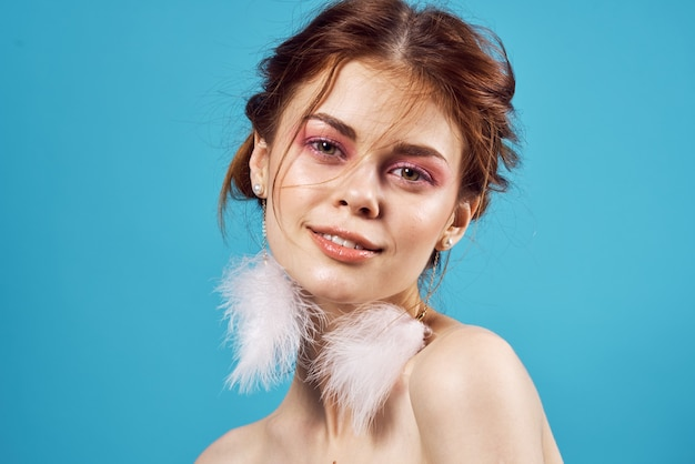 벌거 벗은 어깨를 가진 여자 솜털 귀걸이 화장품 패션 근접 촬영