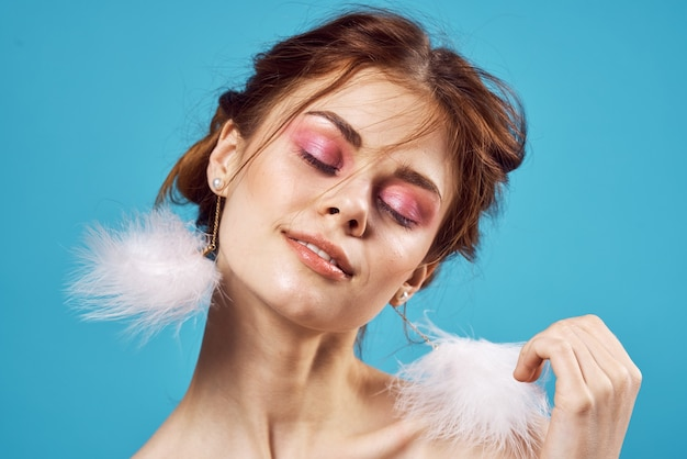 Woman with bare shoulders fluffy earrings cosmetics fashion closeup