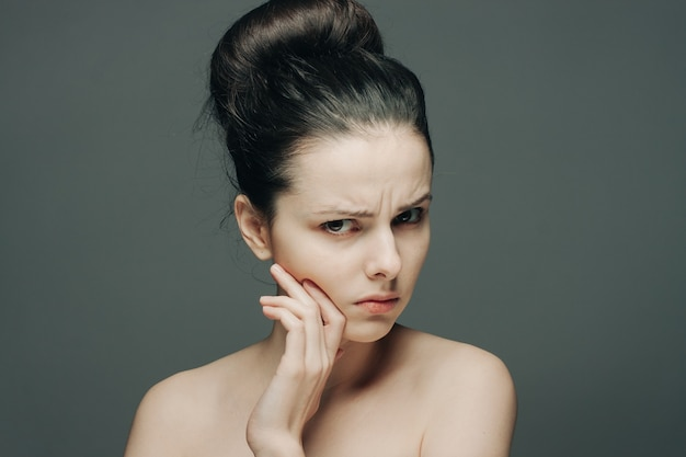 Woman with bare shoulders gathered hair discontent hand on face