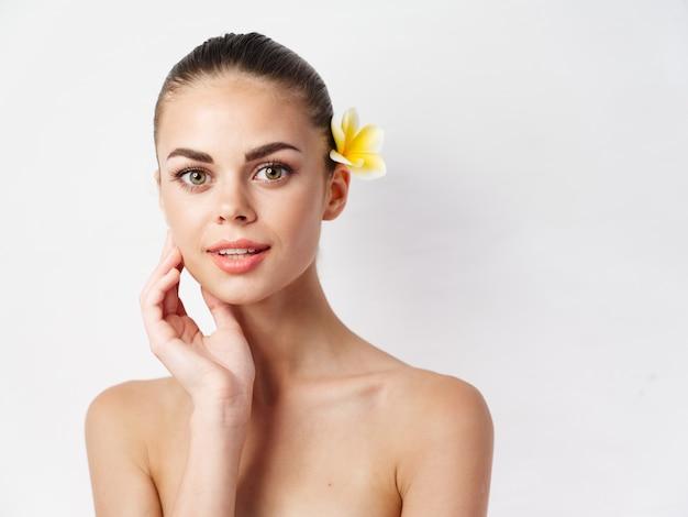 裸の肩を持つ女性は、顔のメイクのきれいな肌の近くに手を握ります