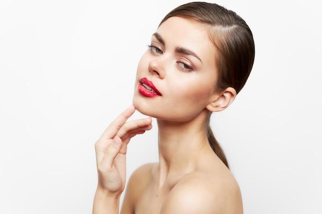 肩がむき出しの女性が顔の近くで手を握り、赤い唇の光を魅力的に見せます