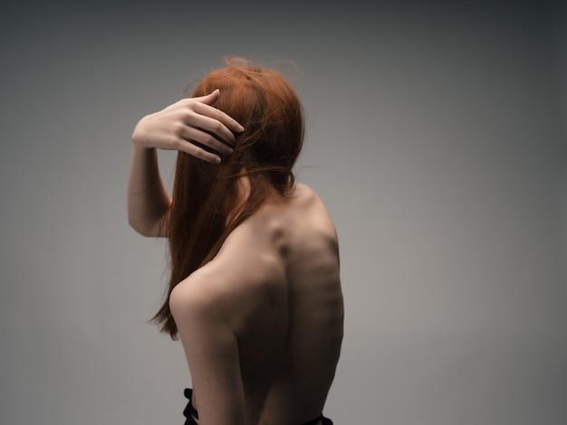赤い髪の孤立した背景をポーズする裸の肩を持つ女性