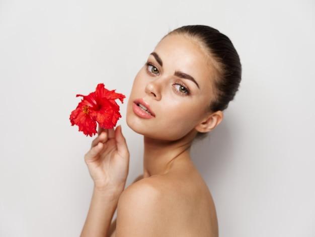 裸の肩を持つ女性赤い花の澄んだ肌のトリミングされたビュー